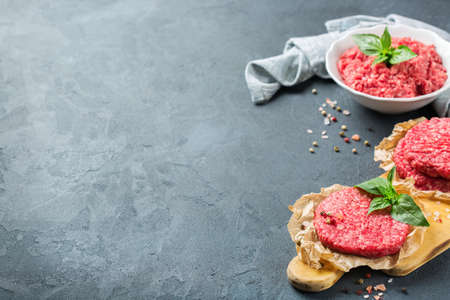 Healthy food, cooking concept. Homemade raw organic minced beef meat and burger cutlet on a grunge black table. Copy space background Stock Photo