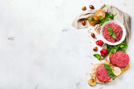 Healthy food, cooking concept. Homemade raw organic minced beef meat and burger steak cutlet with vegetables on a white table. Copy space background, top view flat lay