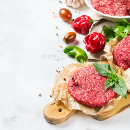 Healthy food, cooking concept. Homemade raw organic minced beef meat and burger steak cutlet with vegetables on a white table. Copy space background