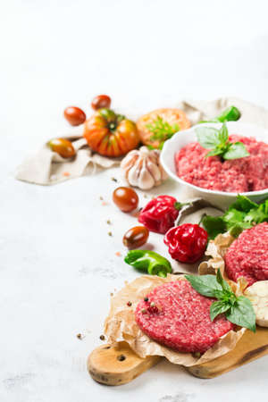 Healthy food, cooking concept. Homemade raw organic minced beef meat and burger steak cutlet with vegetables on a white table