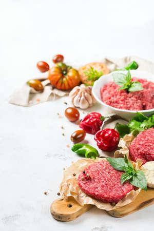 Gezond eten, koken concept. Zelfgemaakte rauwe biologische rundergehakt en hamburger steak kotelet met groenten op een witte tafel