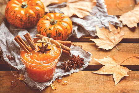 Food and drink, still life, thanksgiving harvest fall autumn concept. Pumpkin jam or confiture with spices on a rustic wooden table. Toned image