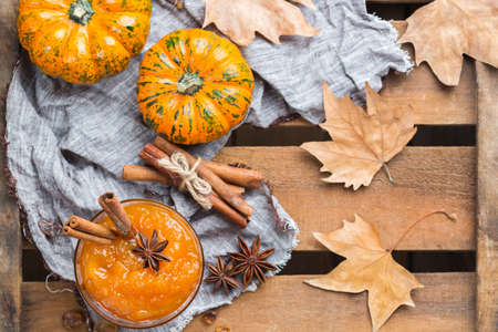 Food and drink, still life, thanksgiving harvest fall autumn concept. Pumpkin jam or confiture with spices on a rustic wooden table. Top view flat lay