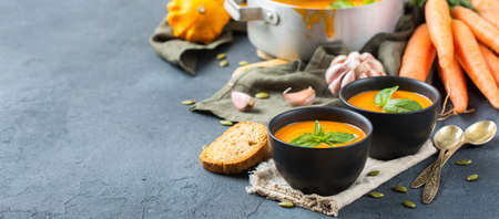 Food and drink, still life, diet and nutrition concept. Seasonal fall autumn roasted orange pumpkin carrot soup with ingredients on a rustic wooden table. Copy space cozy kitchen background Stock Photo