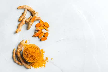 Eten en drinken, dieetvoeding, gezondheidszorgconcept. Organische oranje kurkumawortel en poeder, kurkumalonga op een kokende lijst. Indiase oosterse lage cholesterol kruiden. Ruimte achtergrond, bovenaanzicht kopiëren Stockfoto