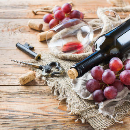 bottle opener: Food and drink, still life, holidays seasonal harvesting fall concept. Bottle, corkscrew, corks, glass of red wine and grapes on a rustic wooden table