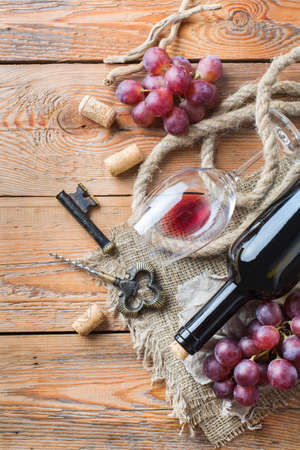 Food and drink, still life, holidays seasonal harvesting fall concept. Bottle, corkscrew, corks, glass of red wine and grapes on a rustic wooden table. Top view flat lay