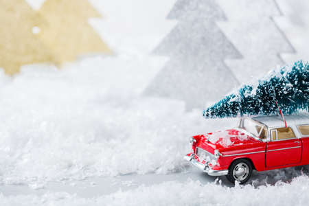 New year holiday concept. Red toy car carrying christmas tree in a snow forest. Copy space greeting card with festive decoration