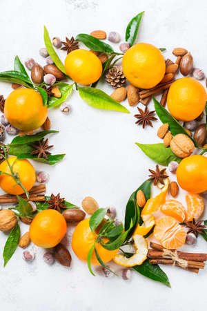 Food and drink, holidays concept. Christmas new year wreath with spices and tangerine on a white rustic table. Copy space top view flat lay background