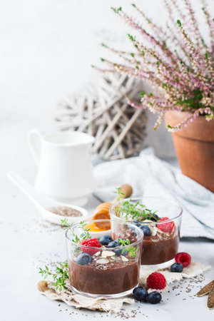 Food and drink, healthy eating and dieting concept. Homemade chocolate chia pudding with fresh berries and green thyme for breakfast on a cozy kitchen table