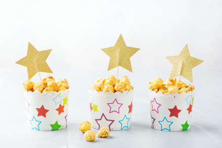 Junk sweet food concept. Portion of caramel popcorn in paper glasses boxes ready for party holidays and cinema Stock Photo