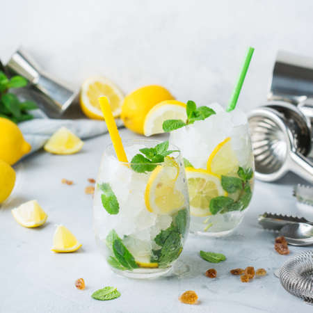 Holidays and party, food and drink concept. Cold alcohol mojito cocktail, long drink beverage, lemonade with lemon, mint and ice in a glass with bartender utensils on a table
