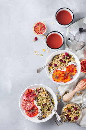Healthy food, diet and nutrition concept. Early morning breakfast with homemade granola muesli, natural yogurt, seasonal ripe blood oranges juice. Top view flat lay copy space kitchen background