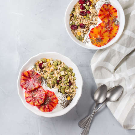 Healthy food, diet and nutrition concept. Early morning breakfast with homemade granola muesli, natural yogurt, seasonal ripe blood oranges. Top view flat lay kitchen background