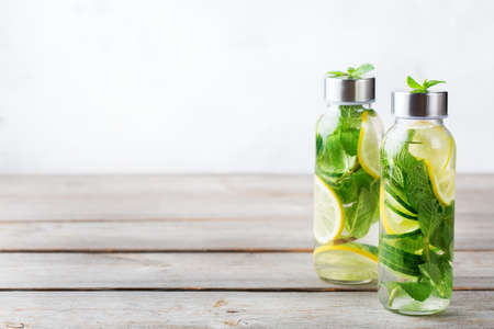 Health care, fitness, healthy nutrition diet concept. Fresh cool lemon cucumber mint infused water, cocktail, detox drink, lemonade in a glass jar for spring summer days. Copy space background Foto de archivo