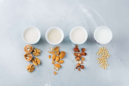 Food and drink, health care, diet and nutrition concept. Assortment of organic vegan non diary milk from nuts in glasses on a kitchen table. Top view flat lay background Stok Fotoğraf