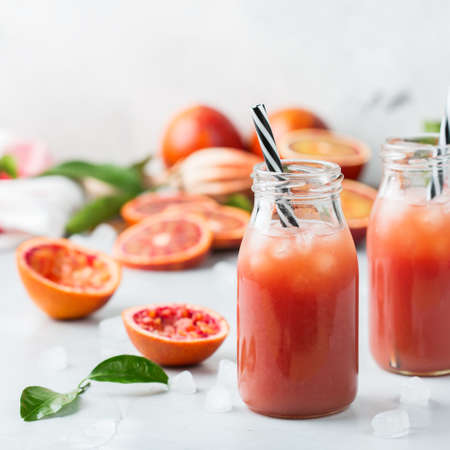 Food and drink, health care, diet and nutrition concept. Fresh red blood orange juice from ripe organic citrus fruits in a bottle for breakfast on a kitchen table. Spring summer beverage