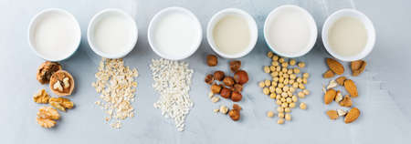 Food and drink, health care, diet and nutrition concept. Assortment of organic vegan non diary milk from nuts, oatmeal, rice, soy in glasses on a kitchen table. Top view flat lay background Stock Photo