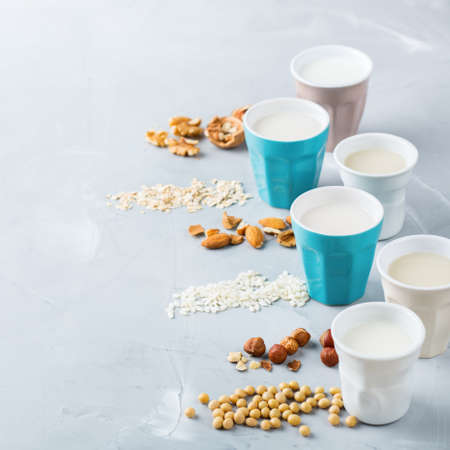 Food and drink, health care, diet and nutrition concept. Assortment of organic vegan non diary milk from nuts, oatmeal, rice, soy in glasses on a kitchen table. Copy space background Stock Photo
