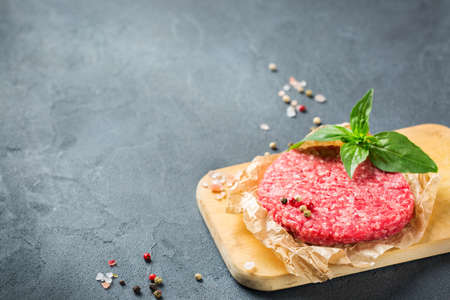 Healthy food, cooking concept. Homemade raw organic minced beef meat burger cutlet on a grunge black table. Copy space background