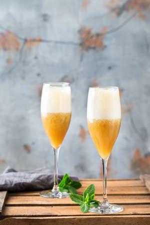 Cibo e bevande, concetto di festa di vacanze. Fresco fresco bevanda alcolica american fizz cocktail in un bicchiere di flauto con rum, champagne, succo di frutta e banana su un tavolo di legno. Copia lo sfondo dello spazio