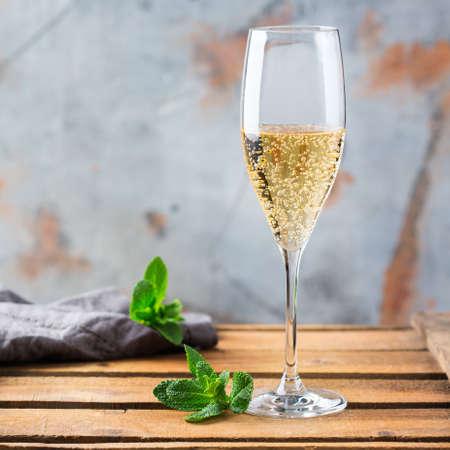 Eten en drinken, vakantie partij concept. Koude verse alcoholische drank champagne mousserende witte wijn met bubbels in een fluitglas op een houten tafel. Kopieer ruimte achtergrond