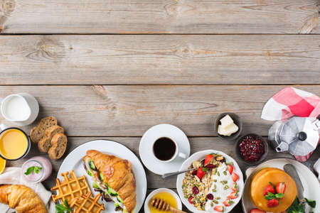 Food and drink, healthy morning eating concept. Breakfast assortment with pancakes, waffles, croissant sandwich and granola with yogurt on the wooden table. Top view flat lay copy space background