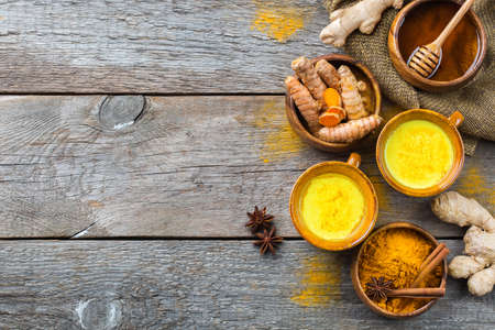 Traditional indian drink turmeric golden milk with ingredients, ginger, curcuma, honey on a rustic wooden table. Top view flat lay copy space background.
