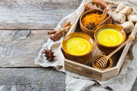 Traditional indian drink turmeric golden milk with ingredients, ginger, curcuma, honey on a rustic wooden table. Copy space background