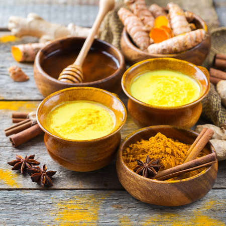 Traditional indian drink turmeric golden milk with ingredients, ginger, curcuma, honey on a rustic wooden table