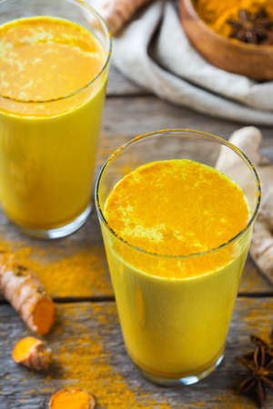 Traditional indian drink turmeric golden milk in a glass with ingredients, ginger, curcuma, honey on a rustic wooden table Stock Photo