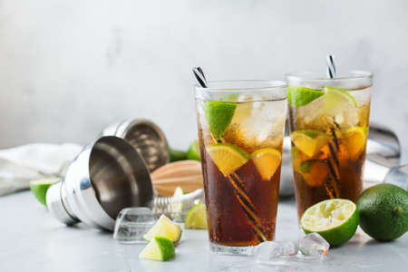 Food and drink, holidays party concept. Cuba libre or long island iced tea alcohol cocktail drink beverage, longdrink in a glass with straw, ice and lime on a table