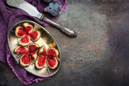Autumn fall harvest concept. Ripe juicy violet figs on a dark rusty kitchen table. Top view flat lay copy space background