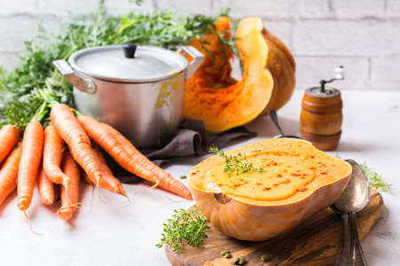 Food and drink, still life, diet and nutrition concept. Seasonal fall autumn roasted orange pumpkin butternut squash carrot soup with ingredients on a table. Cozy kitchen background Stock Photo