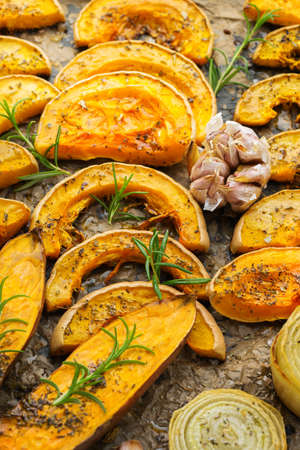 Baked roasted grilled orange pumpkin butternut squash and sweet potato with herbs. Autumn food, soup ingredients. Kitchen background