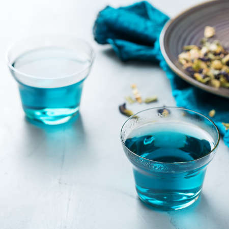 Blue butterfly pea flowers tea in a glass on a table. Healthy detox fitness drink, beverage