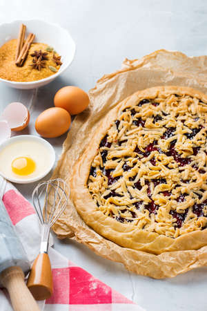 Baking cooking ingredients and utensils with raw berry pie on a kitchen table. Flour, sugar, butter, eggs, spices, honey Foto de archivo