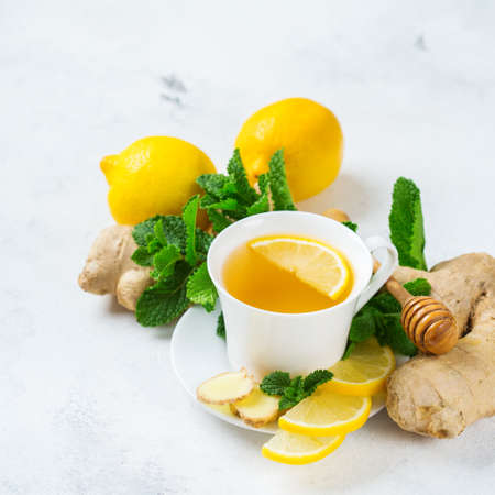 Food and drink, still life health care concept. Ginger tea infusion beverage in white cup with lemon mint honey on a kitchen table for cold and flu winter autumn days Stockfoto