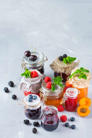 Food and drink, harvest summer autumn concept. Assortment of seasonal berries and fruits jams in jars on a wooden table. Copy space rustic background