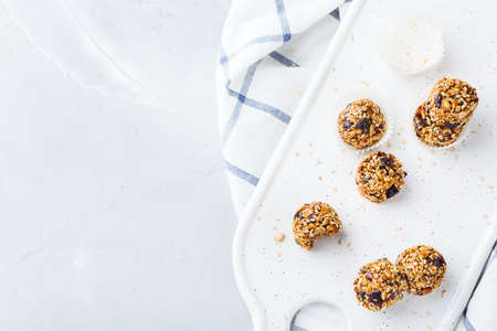 Food and drink, healthy lifestyle, eating, diet and nutrition, snack, superfood concept. Handmade raw vegan protein energy balls with sesame seeds, dry cranberry, nuts, honey.   background