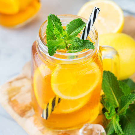 Food and drink, holidays party concept. Lemon mint iced tea cocktail refreshing drink beverage in a mason jar on a table for summer days 스톡 콘텐츠