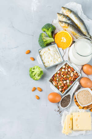 Balanced diet nutrition, healthy eating concept. Assortment of food sources rich in calcium, beans, dairy products, sardines, broccoli, chia seeds, almonds on a kitchen table. Copy space background Standard-Bild - 116892451