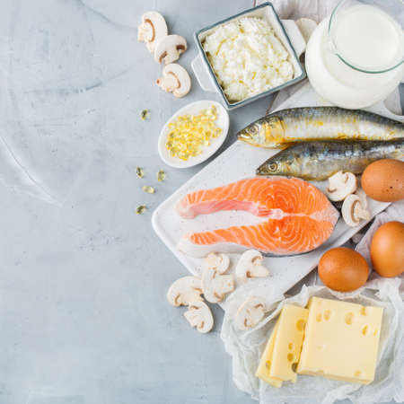 Balanced diet nutrition, healthy eating concept. Assortment of food sources rich in vitamin d, salmon, dairy products, milk, eggs, cheese, mushrooms, sardines on a kitchen table 免版税图像