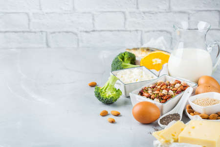 Balanced diet nutrition, healthy eating concept. Assortment of food sources rich in calcium, beans, dairy products, sardines, broccoli, chia seeds, almonds on a kitchen table. Copy space background Archivio Fotografico