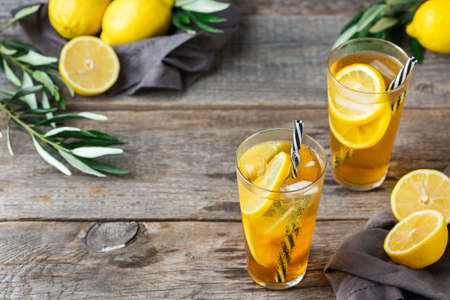 Food and drink, holidays party concept. Lemon mint iced tea cocktail refreshing drink beverage in a glass on a table for summer days. Copy space background Фото со стока
