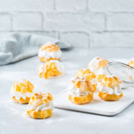 Food and drink, holidays concept. Delicious sweet homemade profiteroles with cream on a modern kitchen table Imagens