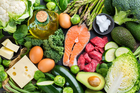 Balanced diet nutrition keto concept. Assortment of healthy ketogenic low carb food ingredients for cooking on a kitchen table. Green vegetables, meat, salmon, cheese, eggs. Top view background Imagens