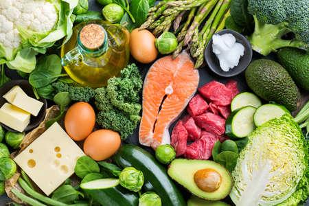Concepto de ceto de nutrición de dieta equilibrada. Surtido de ingredientes alimenticios cetogénicos bajos en carbohidratos saludables para cocinar en la mesa de la cocina. Verduras, carne, salmón, queso, huevos. Fondo de vista superior Foto de archivo
