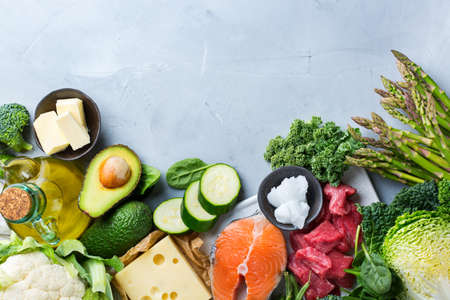 Balanced diet nutrition keto concept. Assortment of healthy ketogenic low carb food ingredients for cooking on a kitchen table. Green vegetables, meat, salmon, cheese, eggs. Top view background Фото со стока