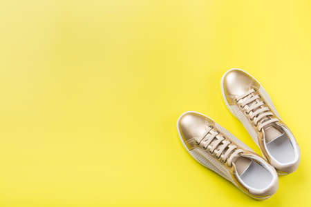 Fashion, blog, blogging, lifestyle, well-being trendy concept. Pair of golden female sneakers on yellow background, top view, copy space, flat lay 스톡 콘텐츠